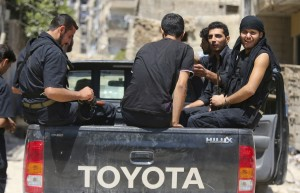 Members of 'Ahrar Dimachk' Brigade, part of the 'Asood Allah' Brigade which operates under the Free Syrian Army sit in a pickup truck on one of the battlefronts in Jobar, Damascus August 25, 2013. REUTERS/ Mohamed Abdullah (SYRIA - Tags: POLITICS CIVIL UNREST CONFLICT) - RTX12WDR