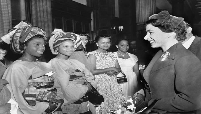 Queen Elizabeth II chats with this pair of colonial students when she visited the British council?s student hostel in London on Dec. 13, 1955, where 350 colonial men and women are students. The occasion of her visit was to help celebrate the 21st anniversary of the council. The two students, dressed in their colorful native garb are, Flanlayo Williams. 22, of Lagos, left, and Miss R. Sekoni Williams, of Ibadan, Nigeria. Others are unidentified. (AP Photo)